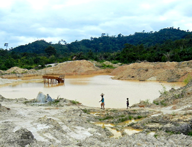 WOMAN AND CHILD WALK PAST HUGE ALLUVIAL PIT MINE
