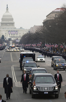 Flanked by Secret Service agents, US President George W. Bush and First Lady, Laura Bush travel the inaugural parade route inside an armored limousine headed toward the White House