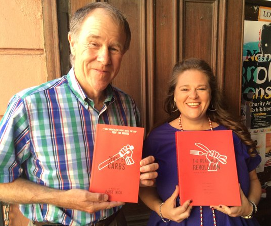 Tim Noakes and Paige Nick holding each other's books.